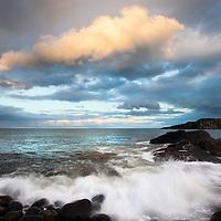 Sunlit Rainclouds over Greymare Rock at Dusk Dunstanburgh Northumberland Coast England
