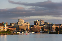 Paddlers race towards the sunset in the Inner Harbour of Victoria, BC as the downtown buildings and the Empress Hotel wait in the distance.