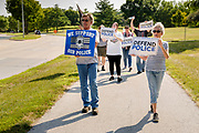 "08 AUGUST 2020 - WEST DES MOINES, IOWA: People walk up Mills Civic Parkway in front of the West Des Moines police station during a rally in support of police and law enforcement. About 100 people gathered at the West Des Moines Law Enforcement Center to rally in support of law enforcement. The rally was organized by ""Uplifting Our Police,"" a local organization that supports law enforcement. They rallied at Des Moines Police headquarters in July. They are planning similar rallies at police stations in the Des Moines metropolitan area.     PHOTO BY JACK KURTZ"