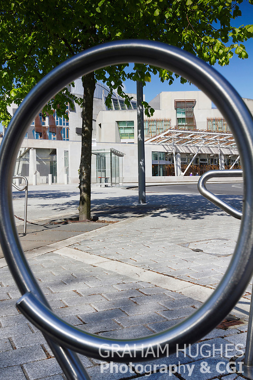 Scottish Parliament Building With Blue Sky And Green Foliage On Trees. Through Bike Rack Circle.