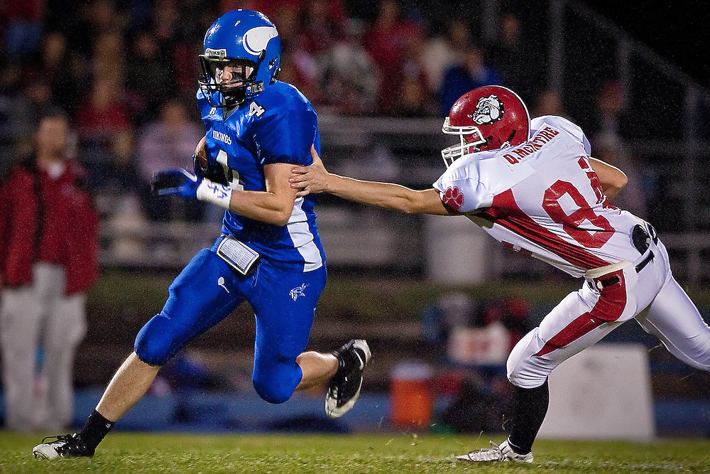 Coeur d'Alene High's Jake Matheson speeds by a reaching Quinn McIntire during a punt return Friday in the Viking's 55-7 win over the Bulldogs.