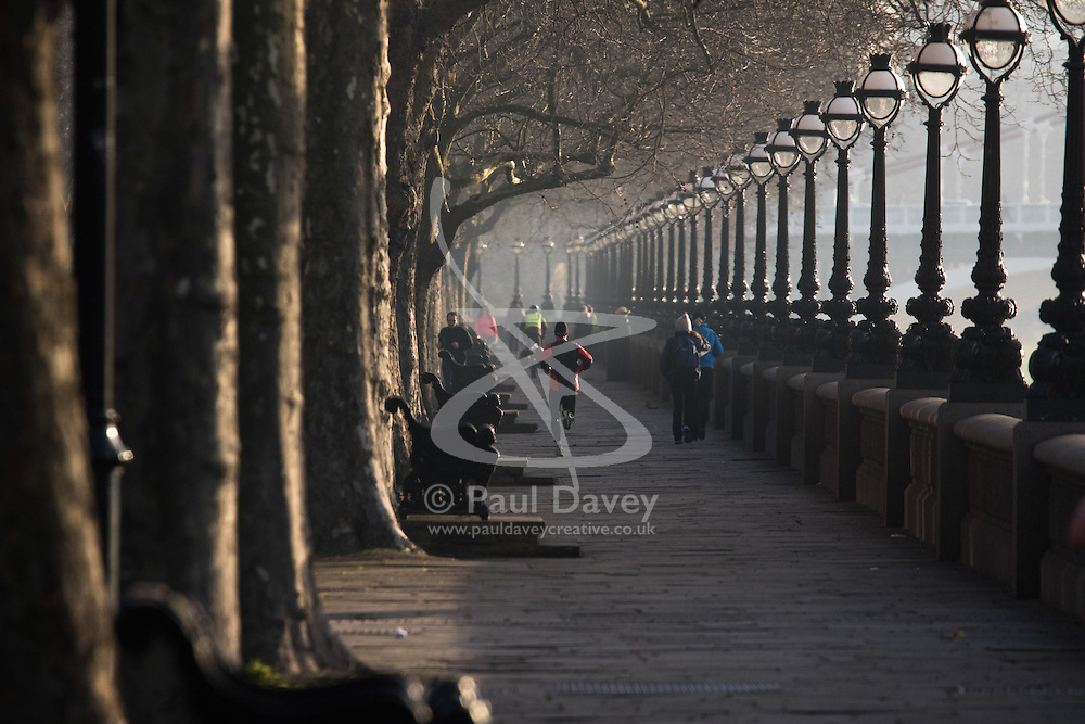 London, February 24th 2016. A runner jogs along the River Thames at Cheyne Walk as the sun rises on a chilly but clear London morning. ///FOR LICENCING CONTACT: paul@pauldaveycreative.co.uk TEL:+44 (0) 7966 016 296 or +44 (0) 20 8969 6875. ©2015 Paul R Davey. All rights reserved.
