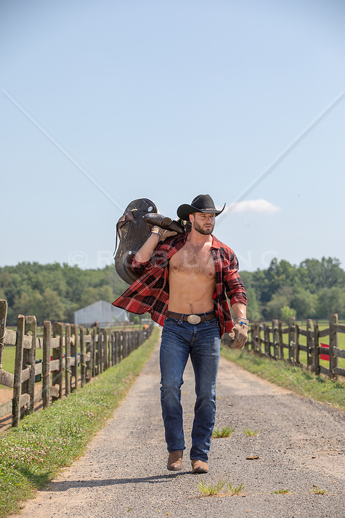 rugged cowboy with open shirt on a ranch