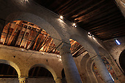 View from below of the cylindrical columns separating the nave from its aisles of Sant Climent de Taull church, 1123, consecrated by Ramon Guillem, the bishop of Roda, Taull, Province of Lleida, Catalonia, Spain. This is a church with three naves separated by cylindrical columns, topped by three semicircular apses. The roof, of two sheds, is built of wood. The cylindrical columns separating the nave from its aisles have no capitals. Sant Climent de Taull is part of the Catalan Romanesque churches of the Vall de Boí which were declared a World Heritage Site by UNESCO in November 2000. Picture by Manuel Cohen.