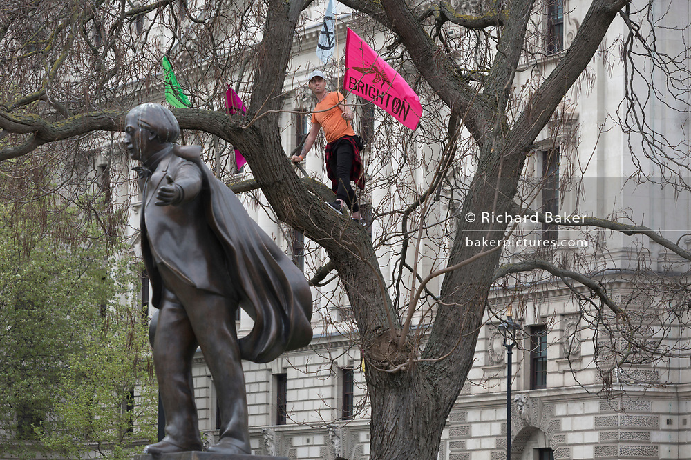 The statue of David Lloyd George 1st Earl Lloyd-George of Dwyfor, OM, PC, the British Liberal politician and statesman and a climate change protester during the week-long action by climate change activists with Extinction Rebellion's campaign to block road junctions and bridges around the capital, on 23rd April 2019, in London England.