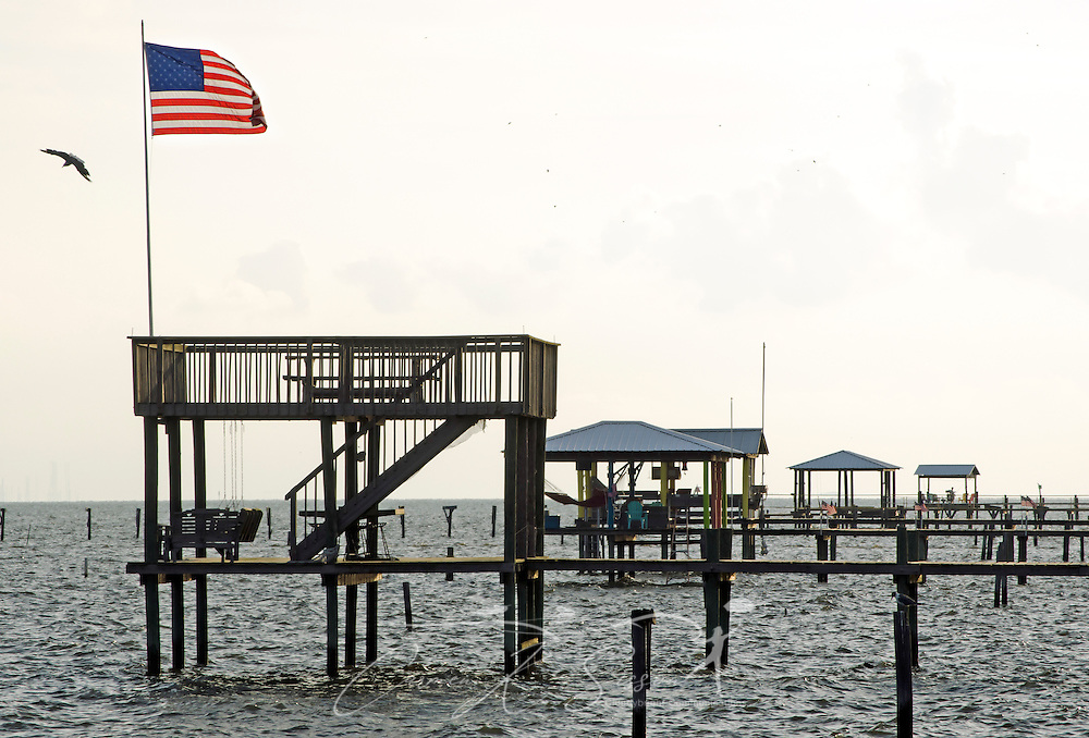 An American flag flies on a wooden pier on Dauphin Island, Alabama. (Photo by Carmen K. Sisson/Cloudybright)