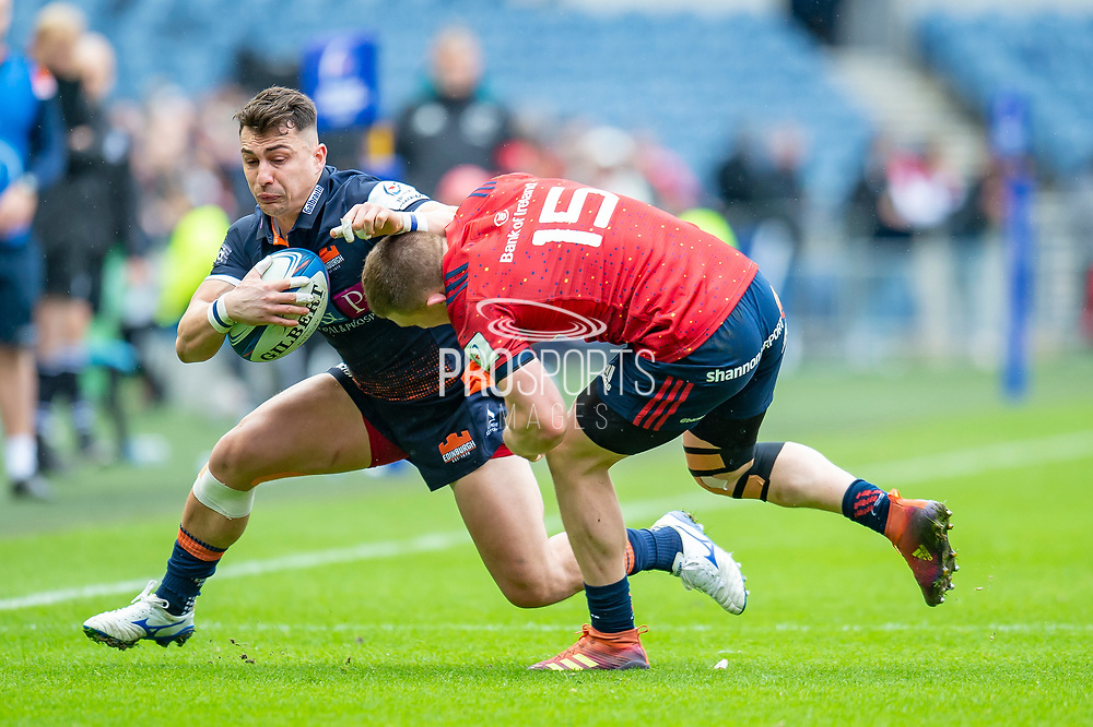 Damien Hoyland (#14) of Edinburgh Rugby tries to shrug off the tackle of Andrew Conway (#15) of Munster Rugby during the Heineken Champions Cup quarter-final match between Edinburgh Rugby and Munster Rugby at BT Murrayfield Stadium, Edinburgh, Scotland on 30 March 2019.