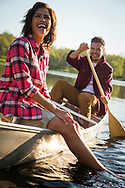 Woolrich Summer and Spring in Maine advertising for national print for couple canoeing on small lake enjoying time on the water with feet dangling in the water.