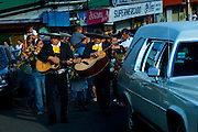Mexican styled mariachi guitarists provide music for a funeral march.