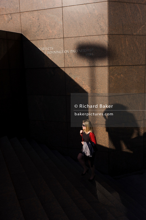 Surrounded by deep shadows, a commuter climbs the steps of number 1 London Bridge.