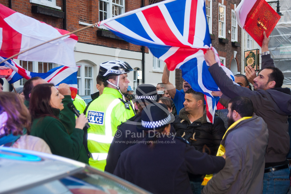 """Mayfair, London, November 28th 2014. A protest against Egypt's leader Al-Sisi descended into moinor scuffles as right wing """"patriots"""" from anti-Islamic group Britain First arrived to protest against the presence of Islamist preacher Anjem Choudary, who was recently arrestred as part of an ant-terror operation. Playing patriotic British Music, Britain First accused Muslims of worshiping a """"devil"""" and a """"paedophile prophet"""". Police had to intervene before hotheads on both sides became violent. PICTURED: A Muslim Activist grabs a British flag from a Britain First protester inciting fury amongst the anti-Islamist group."""