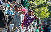 MANDALAY, MYANMAR - CIRCA DECEMBER 2013: Happy Burmese children riding a typical bus in the streets of Amarpura in Myanmar