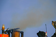 exhaust pipe emitting smoke and fumes from an old maritime diesel engine on a fishing boat
