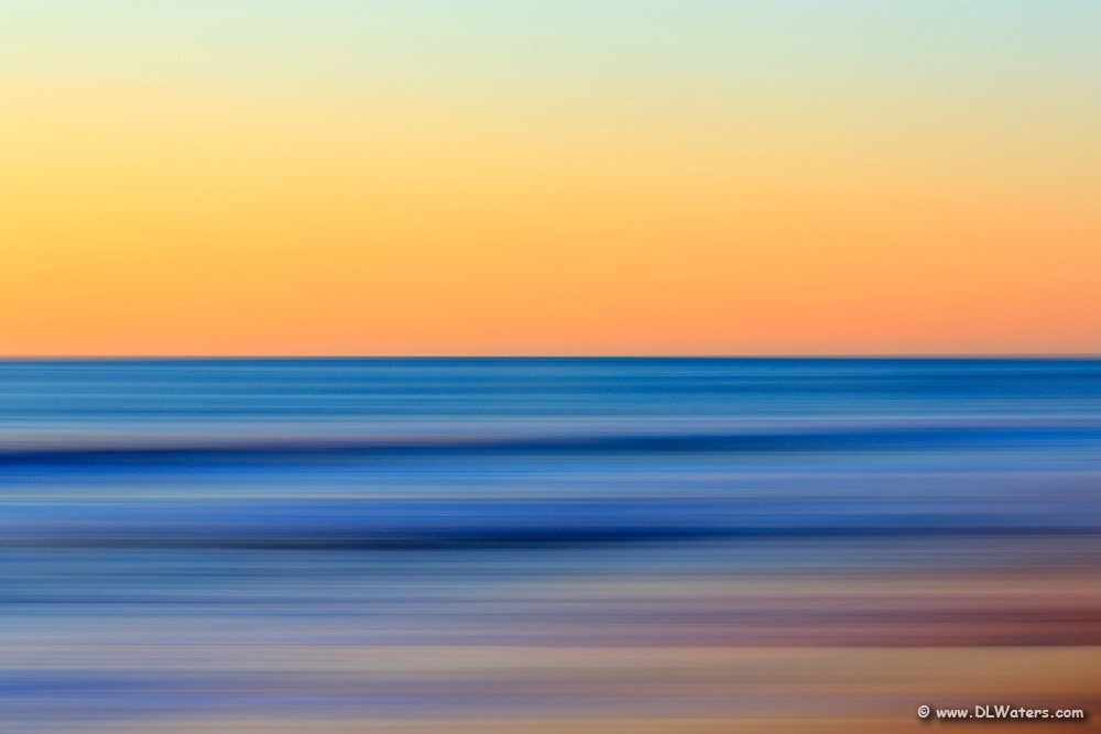 A Outer Banks beach sunrise reduced to colors and lines. Using camera movement during a long exposure to blur the beach and ocean.