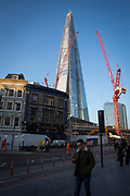 Commuters on Tooley Street with The Shard and The News Building in the background in London, United Kingdom. The iconic design of The Shard was inspired by the spires of London churches and masts of tall, 18th-century ships. <br /> (photo by Andrew Aitchison / In pictures via Getty Images)