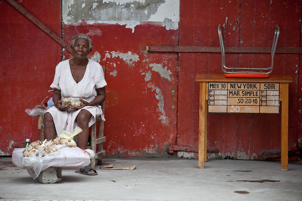 A woman sells peanut brittle next to a betting station on the streets of Les Cayes, Haiti