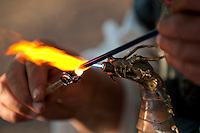 Artisan working with glass and flames in demonstration.
