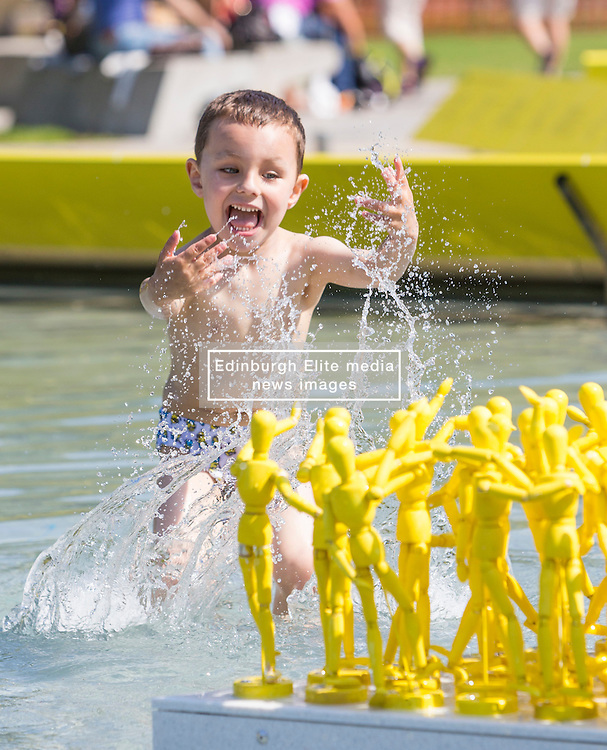 Four year old Samuel Surlit from Edinburgh plays in the ponds in-front of the Scottish Parliament where the Edinburgh International Festival art installation, Anything That Gives Off Light is on display.