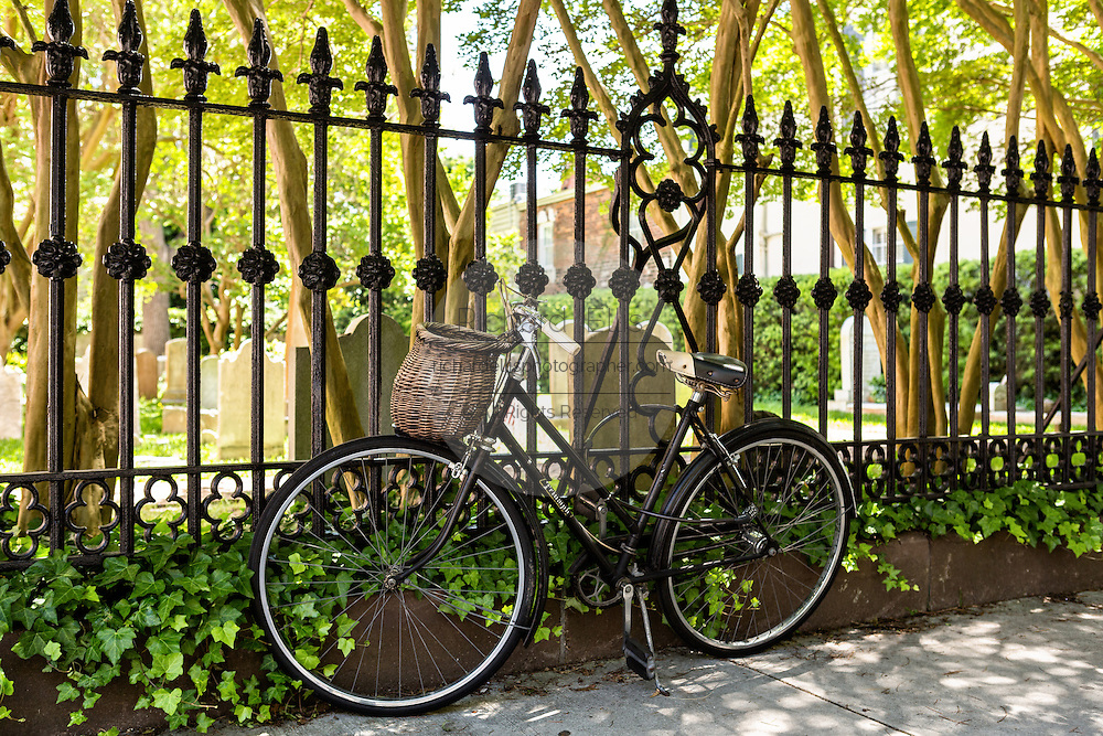 A vintage bicycle chained to the fence of the French Huguenot Church along Church Street in historic Charleston, SC.