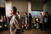 People in need stand a line at the relief soup kitchen in Deir az-Zor. Residents of eastern syrian town Deir az-Zor joined arab spring protests against the regime of Bashar al-Assad from its early beginning in March 2011. Since summer 2012 the town with few hundred thousand inhabitants is embattled between the Syrian Army and different opposing rebel groups like Free Syrian Army and Jabhat al-Nusra. Deir az-Zor is target to constant shelling by artillery, war planes and short range missiles. Almost 70 percent of the town is rebel held while government forces remain in control over some residental areas and a strategic important airport. Deir az-Zor is widely damaged and some areas almost totally destroyed by fierce and long lasting battles. All direct road connections to Deir az-Zor are cut and fighters and returning residents as well depend on one provisional supply line across the Euphrates river which is regularly targeted by government snipers.