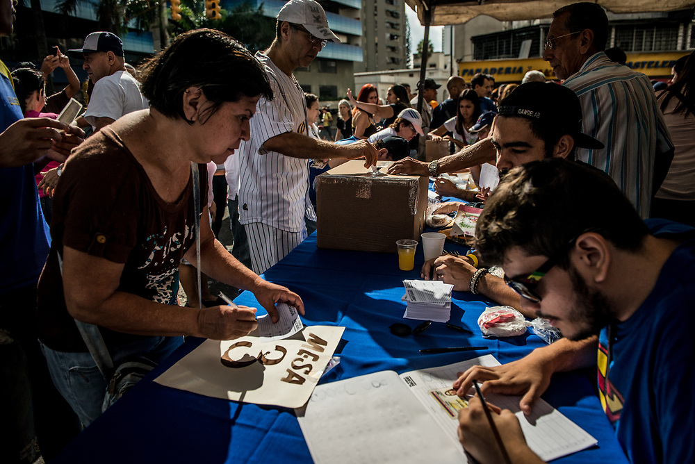 """CARACAS, VENEZUELA - JULY 16, 2017:  Millions of Venezuelans showed up at polling stations at home and abroad on Sunday for a vote unlike any other in this nation's history. They cast ballots with three yes or no questions that were drafted with the aim of weakening President Nicolás Maduro's legitimacy as he sets out to convene a constituent assembly later this month that opponents see a as a power grab by an increasingly unpopular leader. The exercise, known as a """"popular consultation,"""" was organized by a slate of opposition parties that dominate the national assembly. Organizers hope that a large turnout and lopsided result will widen rifts within the ruling party and deepen the government's international isolation, undermining Mr. Maduro's plan to have a hand-picked constituent assembly draft a new charter in coming weeks.  Voters were asked whether they reject the plan to hold a constituent assembly that has not been approved by voters; whether they wanted the country's armed forces to defend the current constitution and the decisions of the opposition-run national assembly; and whether they wanted free elections to pick a new """"national unity government."""" While Mr. Maduro's government is widely expected to ignore the result of the vote, organizers hope it deepens its international isolation and invigorates a protest movement that has gained momentum over the past couple of months. For ordinary Venezuelans, it represented the first opportunity to cast ballots since the 2015 legislative election that ended Mr. Maduro's party's dominance of the national assembly. The government has postponed every election that was scheduled to take place since then. PHOTO: Meridith Kohut"""