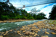 A guide and tourists stand on a suspension bridge over the white waters of the Sarapiqui River in the Tirimbina Biological Reserve.