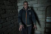 An elderly Iraqi man stands inside his house which was occupied by IS militants since the town of Qayyarah was captured by the terror group in June 2014. He shows his injured hands as a result of a mortar attack outside his home.