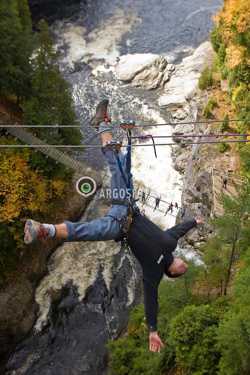 Beaupre, QC, Canada. The aerial traverse at Canyon Sainte-Anne, made of iron wires, from one shore to the other with a safe pulley system / Canion Saint-Anne, localizado a 40 km da cidade de Quebec. Aventura de atravessar o caninon pendurado em um sistema de cabos de aco.