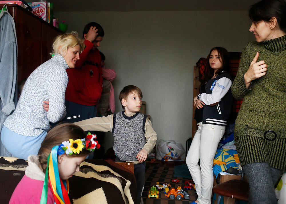 Internally displaced members of two families are seen on February 9, 2015 at a shelter in Artemivsk, Ukraine. At center is a physically disabled young boy who was adopted by the Kovalenko family after his mother abandoned him when the fighting started.