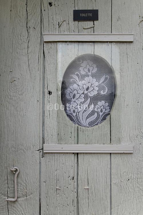 funny toilette window in weathered door