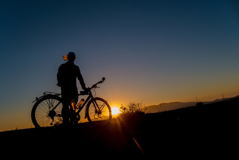 Cyclist and his bike in the sunset, Atacama, Chile