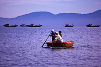 Local fishermen in a tradtional coracle boat return just after dawn with the catch.