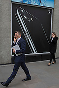 Smartphone users walk past an advert for the Apple iPhone7, on 16th February 2017, in the City of London, England.
