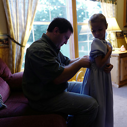 Martin Kauffman helps his six year-old daughter Staci with her traditional mennonite dress in the early morning prior to going to work in Leasburg, Missouri on Tuesday, Sept. 27, 2016. Kaufman is one of a handful of Mennonite families living and working in the area. (Photo by Keith Birmingham Photography)