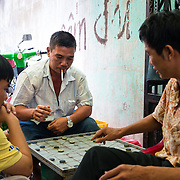 Men playing a game of Chinese chess in an allyway at a market in Saigon