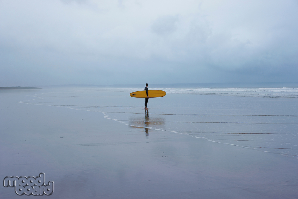 Lone surfer standing in shallow water side view