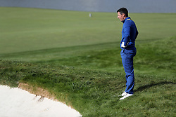 Team Europe's Rory McIlroy looks at his ball in a bunker on the 18th during the Singles match on day three of the Ryder Cup at Le Golf National, Saint-Quentin-en-Yvelines, Paris.