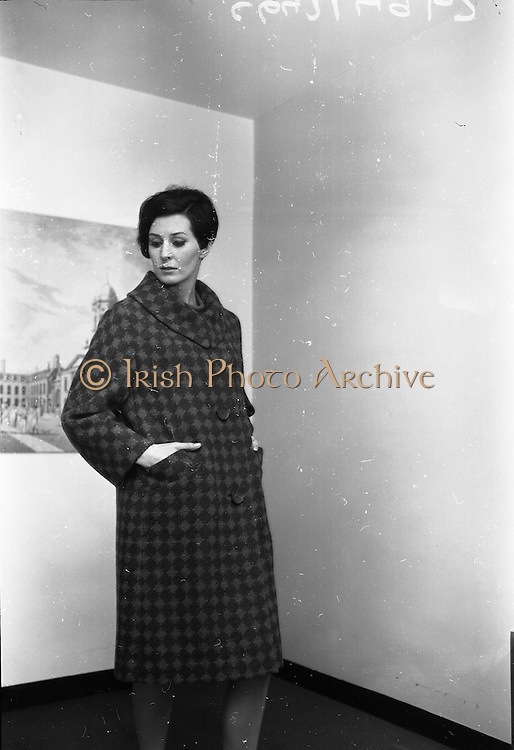 """18/04/1966<br /> 04/18/1966<br /> 18 April 1966<br /> Stands and Models at the 3rd Irish Export Fashion Fair at the Intercontinental Hotel, Dublin. Model wearing """"Shandon"""" a red and green and check coat by Elizabeth James of Cork."""
