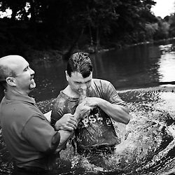 """Michael DuVal (left), Lead Pastor for the Journey Church, lifts Ken Doss from the waters of the Roanoke River during a river baptism at Green Hill Park on Sunday evening. Ken was one of seven people who were baptized in the river on Sunday. A """"believer's baptism"""" they call it, an immersion into faith. The tea-colored water glides over the seven who've chosen tonight, carefully picking their way over the slippery Roanoke River stones. Some are alone; some are families, in a public embrace of Christ. """"Because before Christ, I was living week to week"""". """"Because I used to get impatient when someone took 20 items in the checkout line, and now I'm calm"""". """"Because a follower of Christ doesn't need to look like he has a 'stick up his butt'"""". """"Because now I know there's a greater plan for my life"""". Wading waist deep, clasping the pastors' arm, each says words and is held, briefly, then dunked backwards. One man thrusts his fist in the air and yells to anyone who can hear: """"I'm wet!"""""""