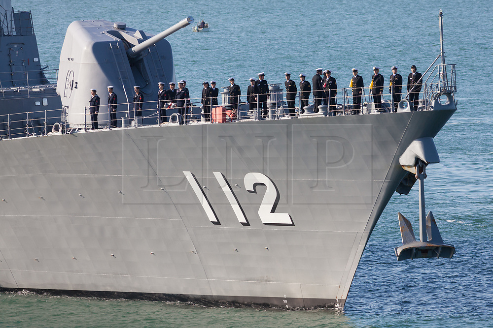 © Licensed to London News Pictures. 25/08/2018. Portsmouth, UK.  Crew aboard the 151-metre long destroyer JS Makinami (112) from the Japanese Maritime Self Defense Force (JMSDF) arriving in Portsmouth this morning, 25th August 2018.  This vessel and the 143-metre long cadet training vessel JS Kashima (3508) have recently conducted a passing exercise (PASSEX) with Standing NATO Maritime Group One (SNMG1) in the Baltic Sea. The ships will moor alongside in Portsmouth Naval Base and be opened to visitors over the bank holiday weekend until 28th August 2018. Photo credit: Rob Arnold/LNP