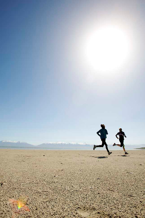 Two runners on Great Salt Lake in the afternoon hitting a perfect stride