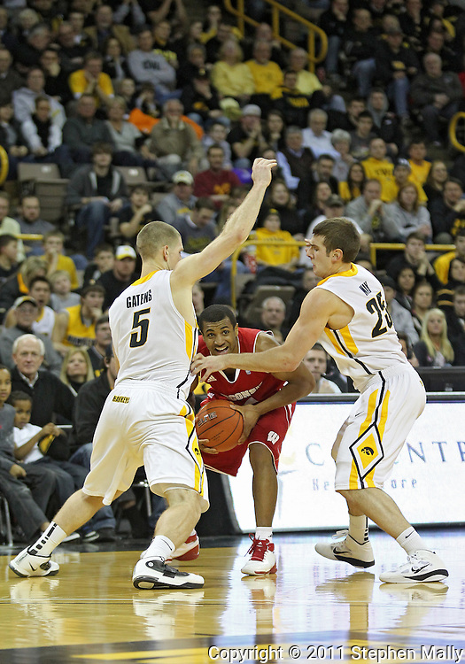 February 09 2011: Wisconsin Badgers guard Jordan Taylor (11) tries to keep the ball away from Iowa Hawkeyes guard Matt Gatens (5) and Iowa Hawkeyes guard/forward Eric May (25) during the first half of an NCAA college basketball game at Carver-Hawkeye Arena in Iowa City, Iowa on February 9, 2011. Wisconsin defeated Iowa 62-59.