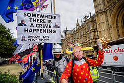 © Licensed to London News Pictures. 03/09/2019. London, UK. Charlie Rome, 35 from Charlton dressed as Robocop holds a banner reading 'Somewhere there is a crime Happening' with with Jef, 47 from Hammersmith dressed as a Boris Johnson clown. Protesters assemble opposite the Palace of Westminster at the beginning a long day as MPs meet to block the suspension of Parliament.  Photo credit: Guilhem Baker/LNP