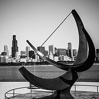 Black and white Chicago Adler Planetarium sundial named Man Enters the Cosmos with the Chicago downtown skyline and Willis Tower (Sears Tower) in the background.