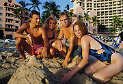 Couples on beach building sandcastle, Waikiki, Oahu Hawaii