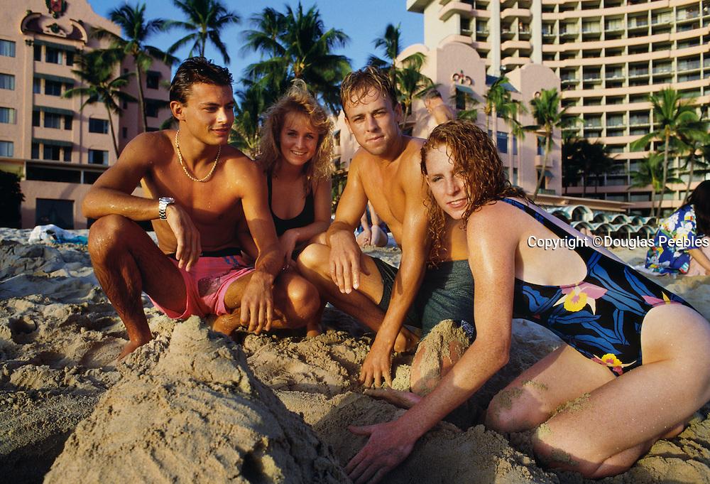 Couples on beach building sandcastle, Waikiki, Oahu Hawaii