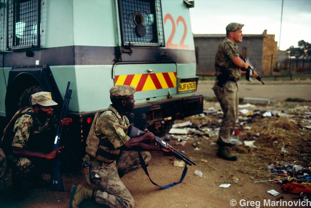 Ratanda, Heidelberg, Transvaal, South Africa. Riot police react during clashes between Xhosa warriors loyal to the ANC and Zulus loyal to the IFP. After the storm, the IFP men came out with intelezi imuti and the vastly numerically superior Xhosa and township residents fled.