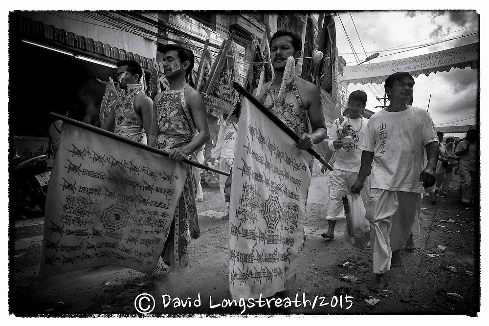 """Devotees to the Chinese Shrine of Ban Tha Rue walk in a street procession in Phuket, Thailand, Sunday, Oc. 18, 2015.  The annual Vegetarian Festival and its accompanying sacred rituals are believed to bestow good fortune on those who practice the religious rites. During the 9 day festival in Phuket Town and surrounding communities which are made up mainly of Chinese desendants, residents observe a strict vegetarian or vegan diet that is suppose to cleanse and grant merit. Sacred rituals where men and women devotees known as """"Mah Song"""" or """"Spirit Horses"""", work themselves into trances to have all manner of knives, daggers, swords or other items pierced through their cheeks. It is believed that they experience no pain while in the trance. This gruesome from of mortification is what most westerners know of the festival. Devotees also walk barefooted over massive mounds of burring coals and climb ladders that have bladed rungs, all with no effect.  (AP Photo/David Longstreath/str)"""