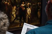 Buitenlandse toeristen bekijken het beroemde schilderij de Nachtwacht van Rembrandt van Rijn
