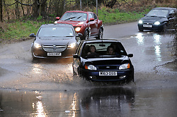 © Licensed to London News Pictures. 5/02/2014<br /> Wet and windy weather conditions continue across the UK. <br /> Cars slow down for Flood water on the A225 near Shoreham in Kent.<br /> Photo credit :Grant Falvey/LNP